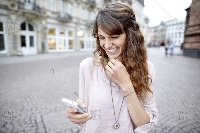 Happy young woman in the city looking at cell phone