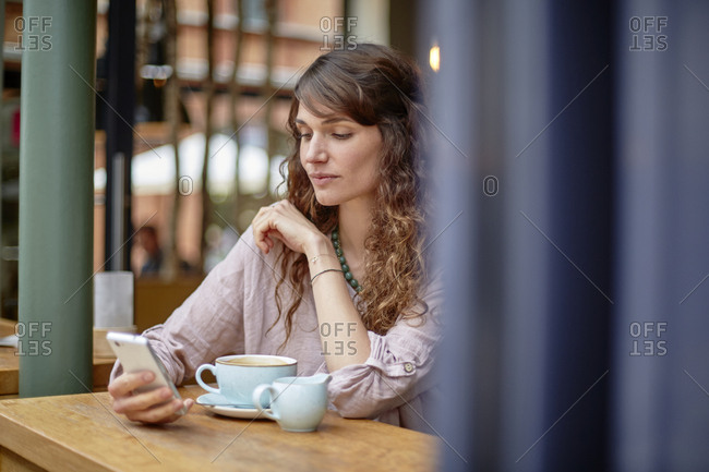 Young woman in a cafe looking at cell phone
