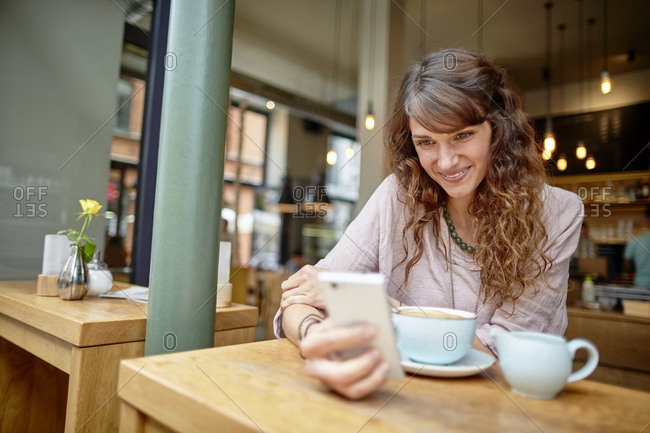 Smiling young woman in a cafe looking at cell phone