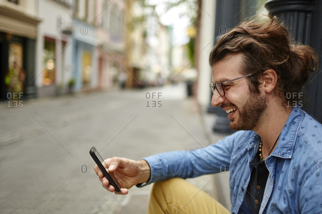 Smiling young man looking at cell phone