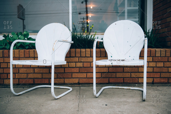 Two vintage, white patio chairs