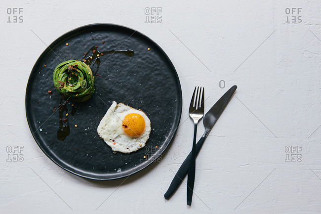 Sunny-side up egg with an avocado rosette