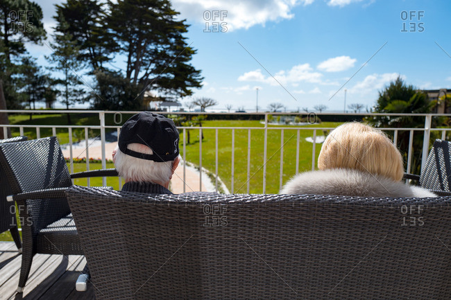 Senior couple sitting together looking out at coast of France