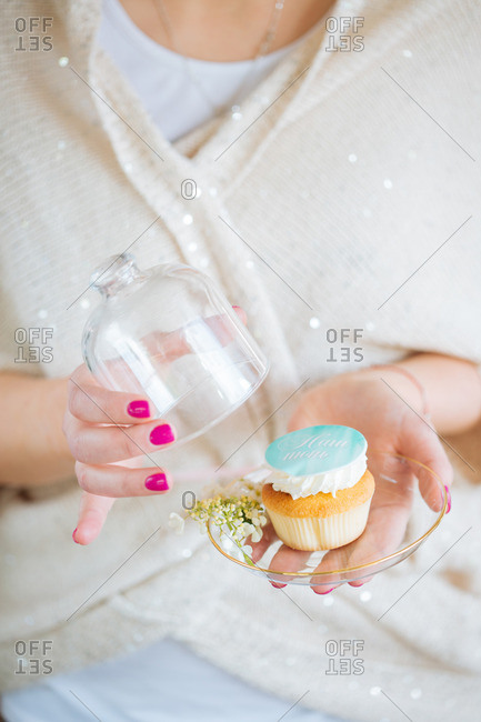 Woman holding cupcake with glass cover
