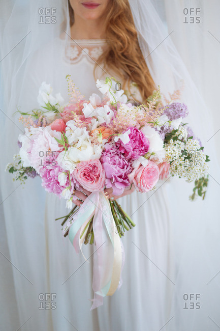 Bride holding a rose and floral bouquet