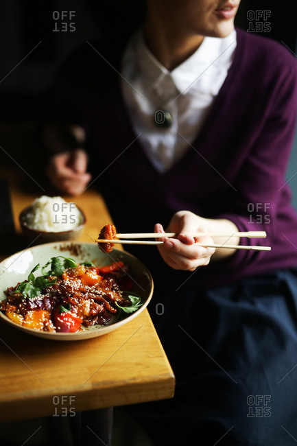 Woman eating dish with chopsticks