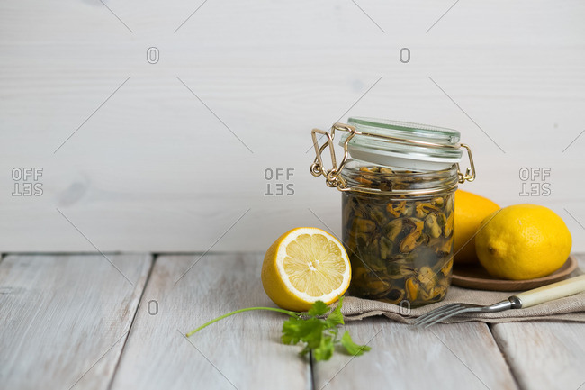 A jar with mussels by lemons