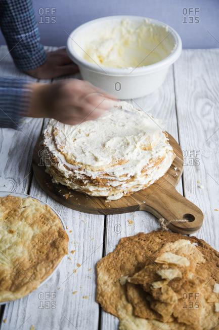Hand making cream and puff pastry cake