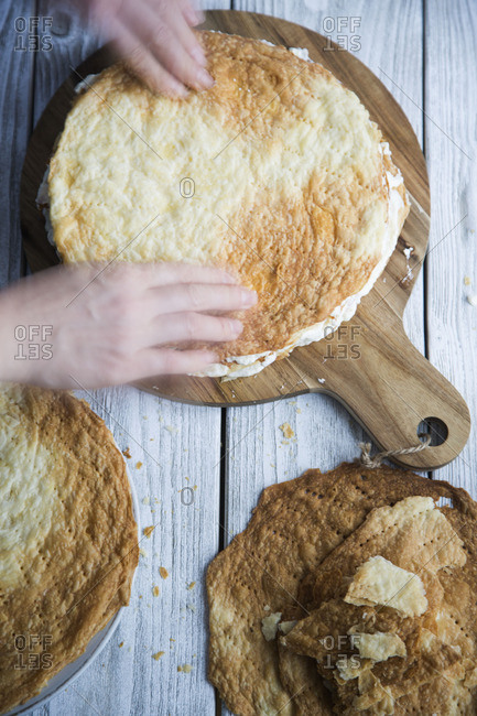 Person assembling puff pastry and cream cake