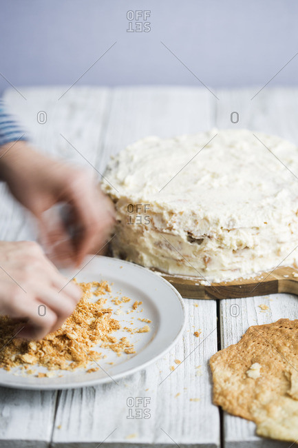 Hand grabbing crumbles by mille feuille cake