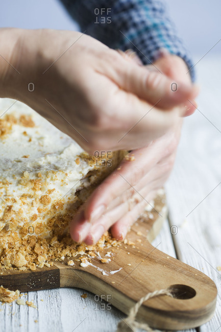 Hand sprinkling crumbles on a cake