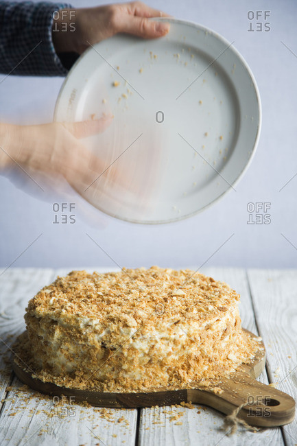 Hand putting crumbles on cake