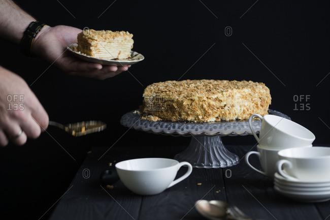 Hands serving mille feuille cake