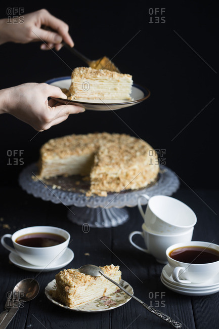 Hand serving cake with tea