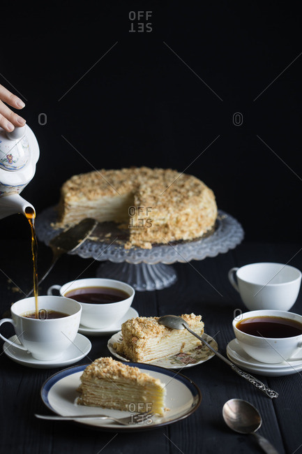 Hand pouring tea with cake
