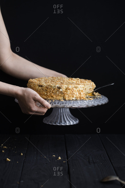 Hand picking up stand with cake