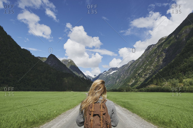 Backpacking woman travels on road