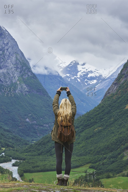 Woman taking photos on smart phone of glacial valley landscape