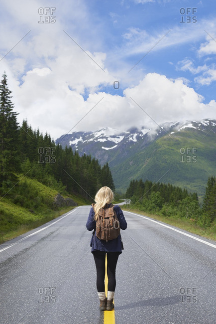 Backpacking woman travels on road in epic majestic mountain