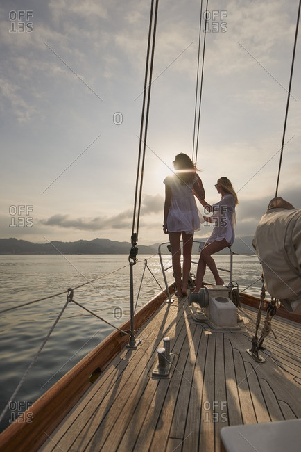 Beautiful girl friends on sailboat at sunset in ocean