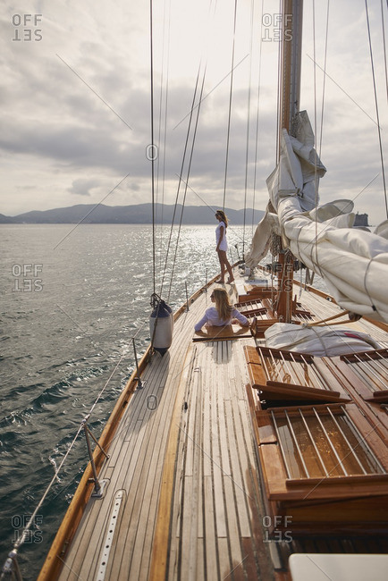 Beautiful girl friends on sailboat in ocean