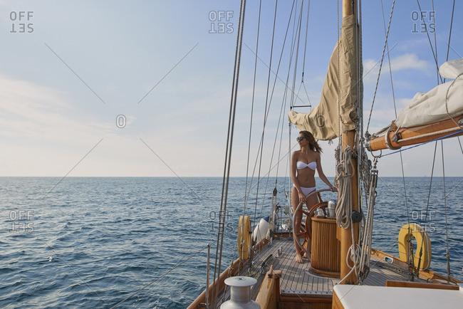 Beautiful  woman steering luxury sailboat in ocean