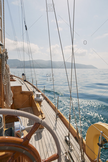 Wooden luxury sailboat sailing over ocean
