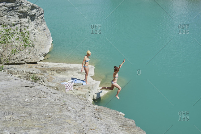 Girls jumping onto beautiful blue freshwater river