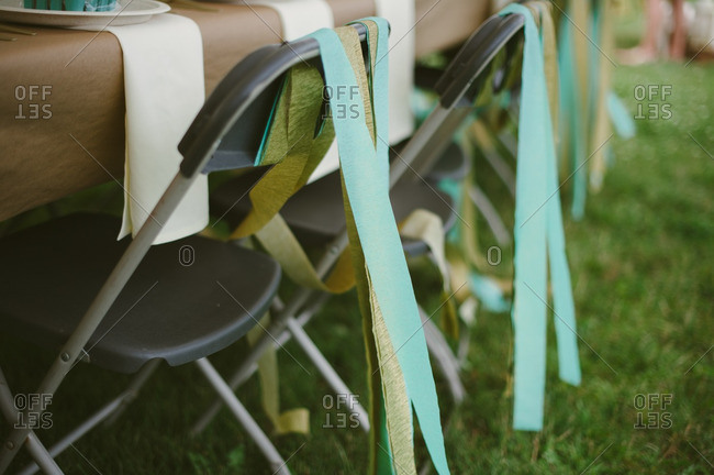 Streamers hanging from chairs at a backyard bridal shower