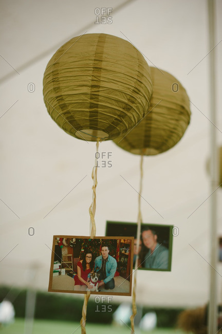 Paper lanterns with hanging photos at a bridal shower