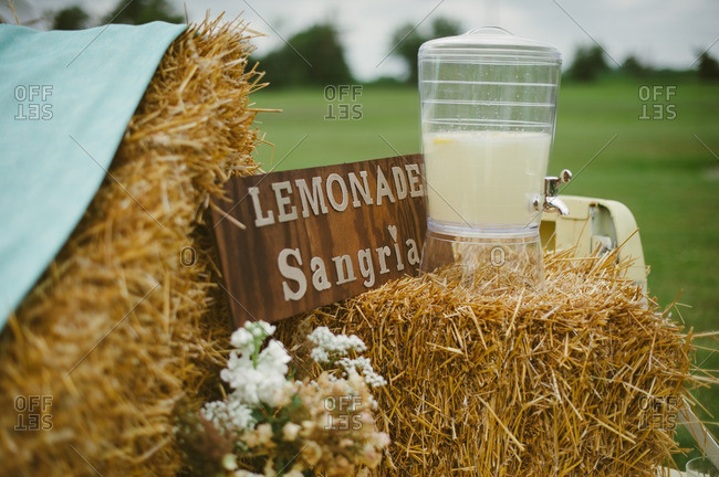 Pitcher filled with lemonade sangria on a bale of hay