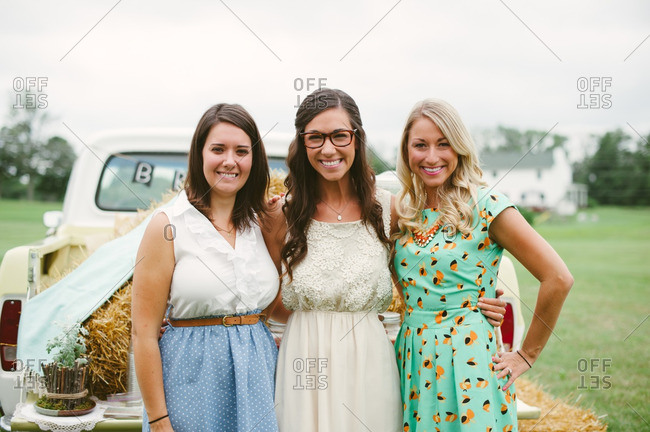 Portrait of three young woman standing by vintage pickup truck