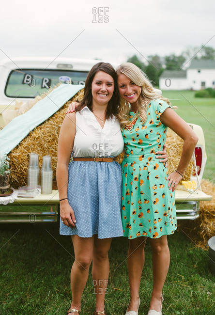 Portrait of two young woman standing by vintage pickup truck