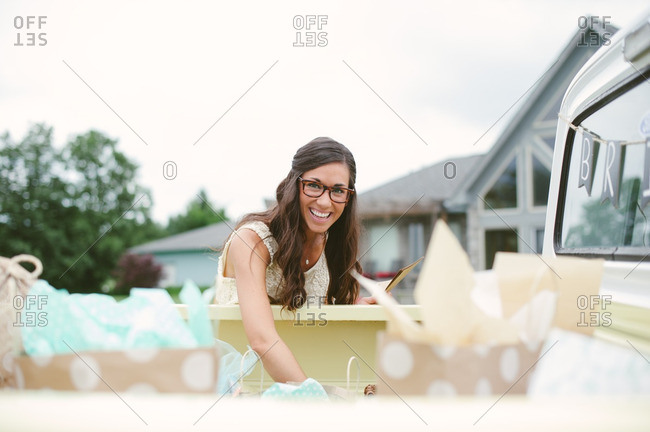 Bride reaching into the back of a pickup truck at her bridal shower