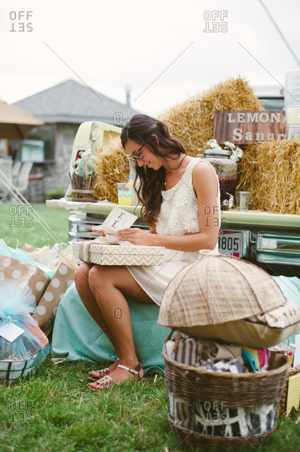 Young woman sitting by a pickup truck at her bridal shower opening gifts and reading cards