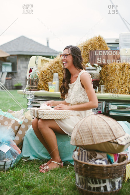 Bride sitting by a pickup truck at her bridal shower opening gifts