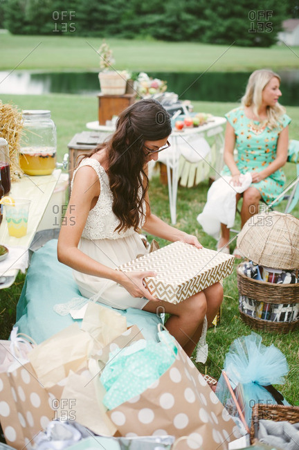 Young bride at her bridal shower opening gifts