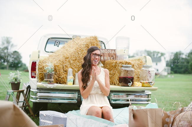 Bride sitting by a pickup truck at her bridal shower laughing while opening gifts
