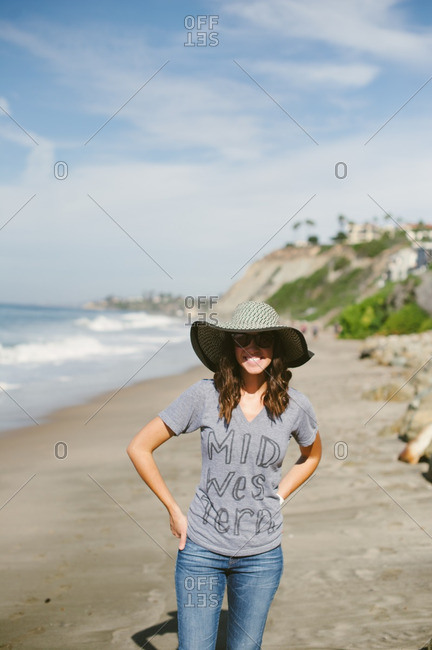 Young woman standing on the coast of California wearing a hat and sunglasses