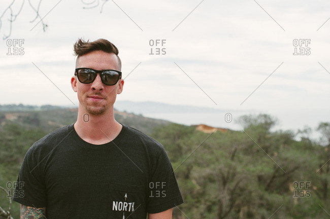Young man with sunglasses standing on the coast of California