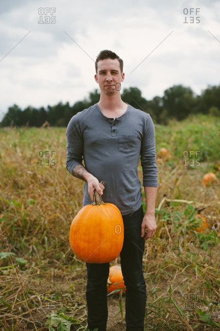 Young man holding a pumpkin in a field