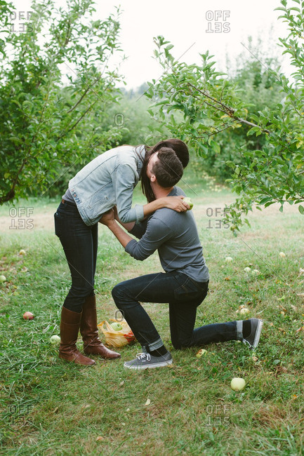 Couple kissing during a proposal in an apple orchard
