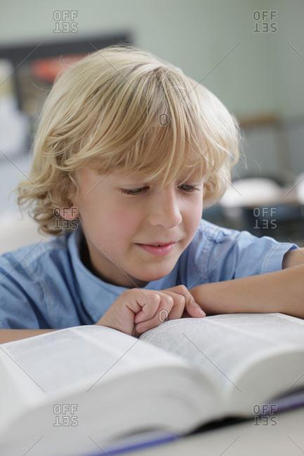 School boy reading book in class