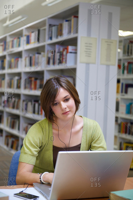 Young woman working on laptop in library