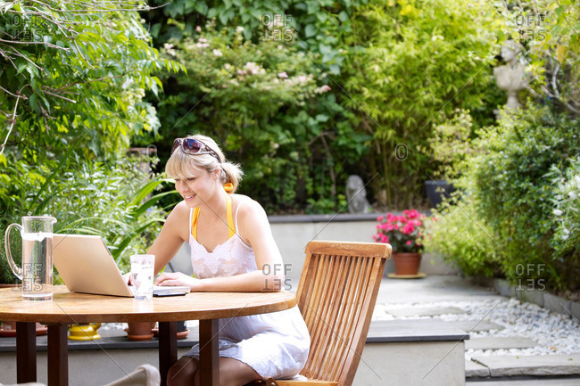 Young woman at garden table on laptop