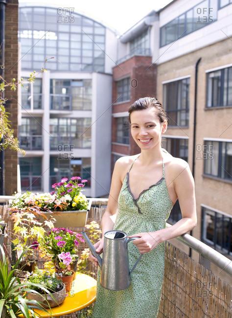 Woman on balcony watering flowers