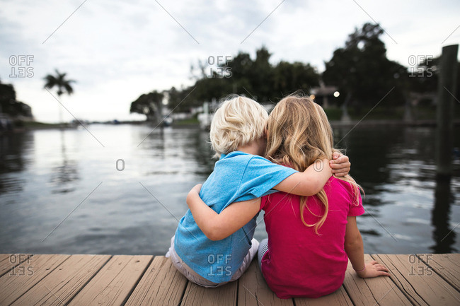 Little boy and girl hug on a dock by the water