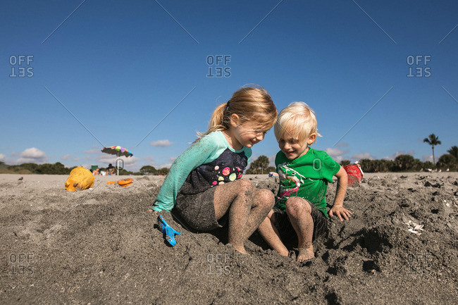 young children have fun getting sandy at the beach