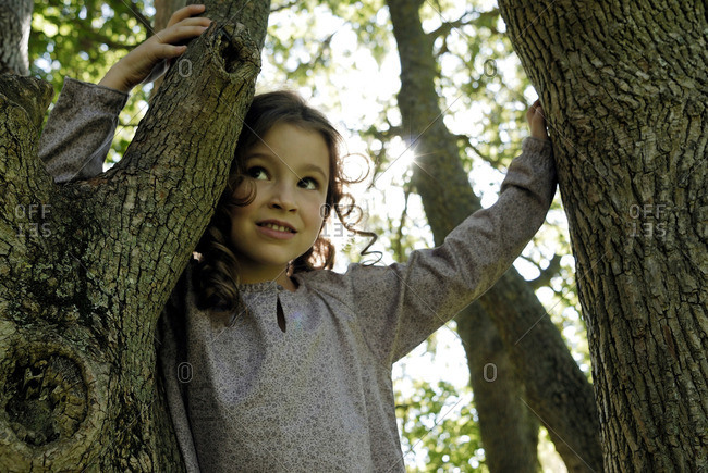 5 years old girl standing by a tree