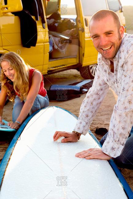 Couple waxing surfboards near a van